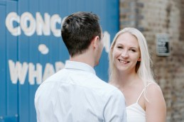 Blonde woman staring at camera over her fiancé's shoulder