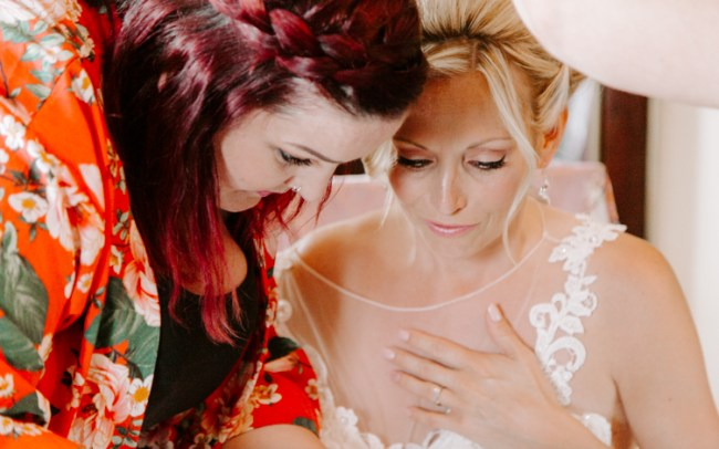 Bride looking emotional while looking in the mirror during preparation for her wedding