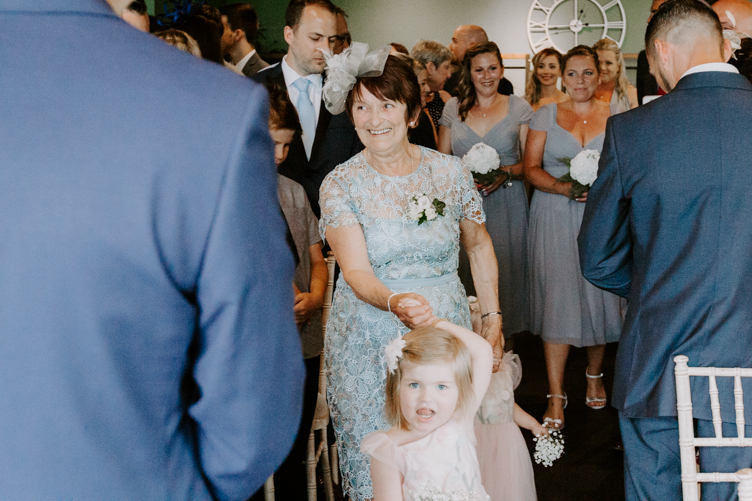 Mother of the Bride in blue walking down the aisle with a cute flower girl