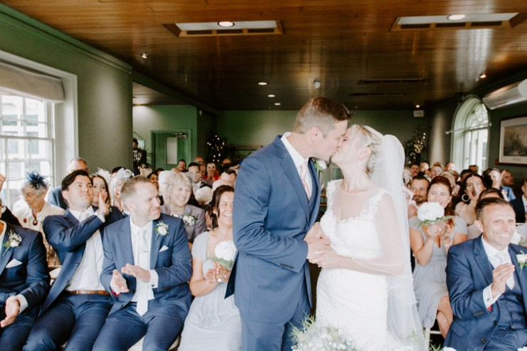 First kiss at wedding with family clapping around the couple