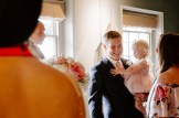 Groom holding his baby daughter and smiling