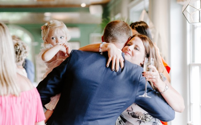 Groom embracing family friend at wedding