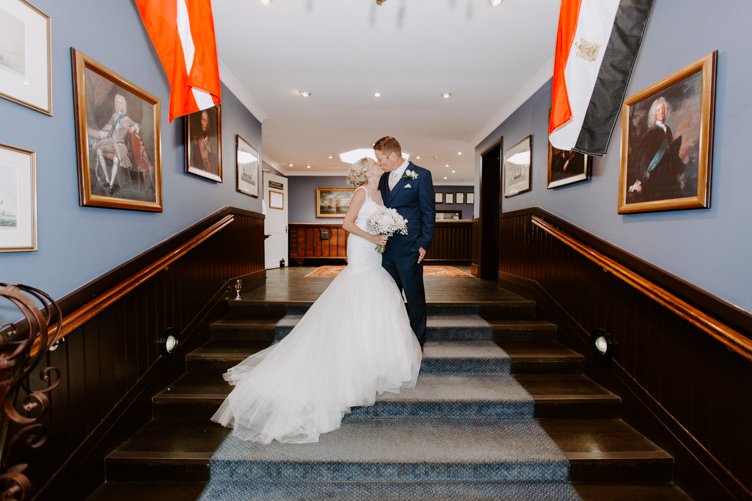 Portrait of a couple kissing on their wedding day on some grand wooden steps