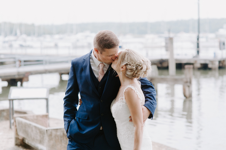 Bride and groom kissing next to a marina at Bucklers Hard