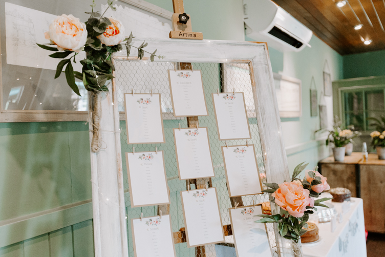 DIY wedding tableplan with pink flowers attached