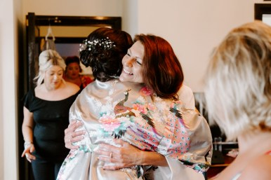 Female wedding guest embracing family member during bridal prep