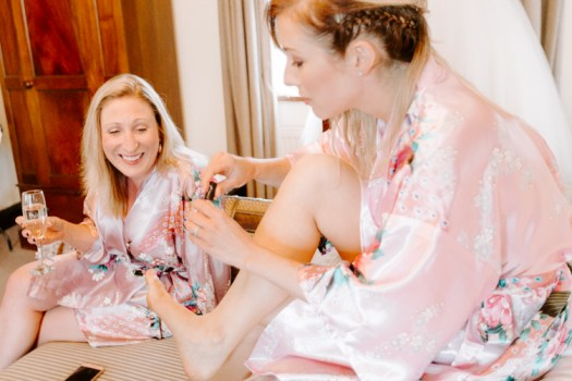 Bridesmaid painting her toe nails in pink silk robe
