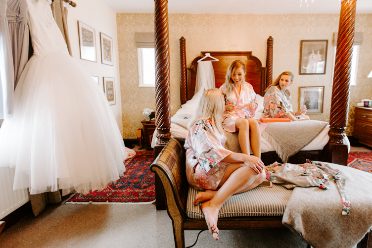 Bridesmaids sat on four poster bed at the Master Builder's wedding venue