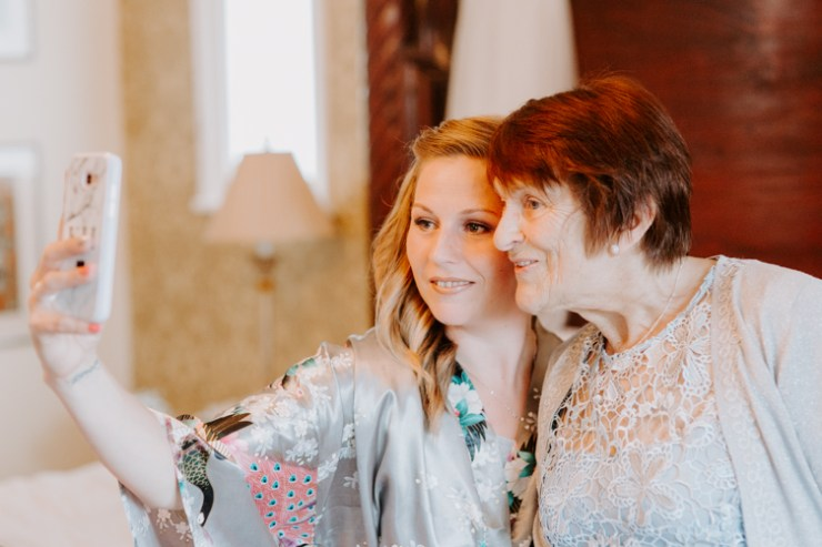 Bridesmaid in silk robe taking a selfie with her Mother