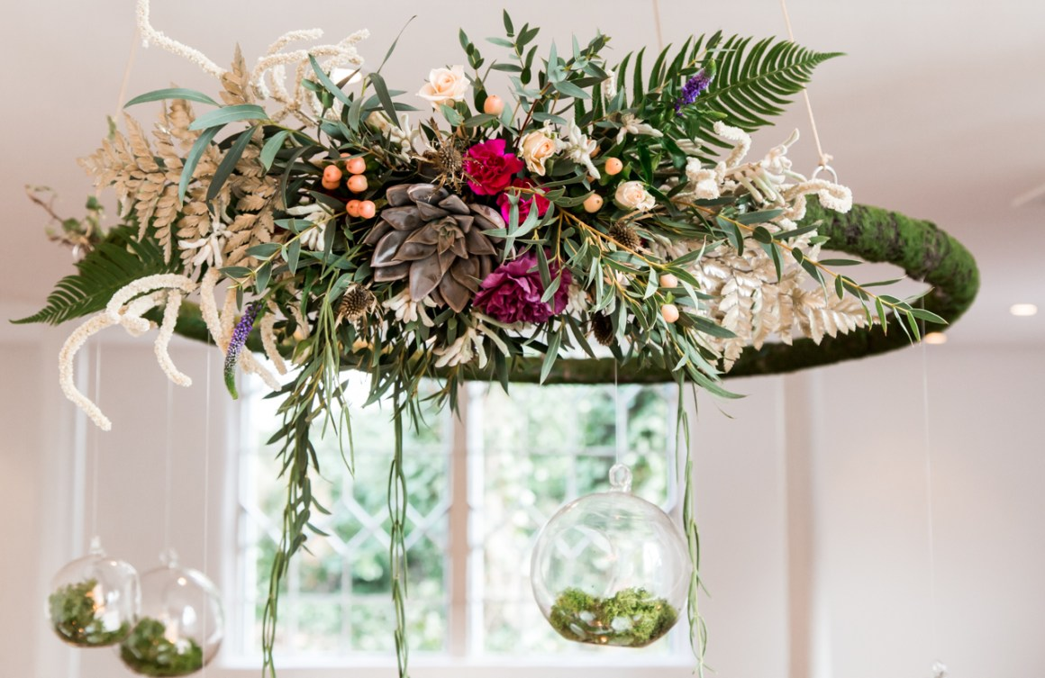 A large hanging foliage hoop with pink and purple flowers