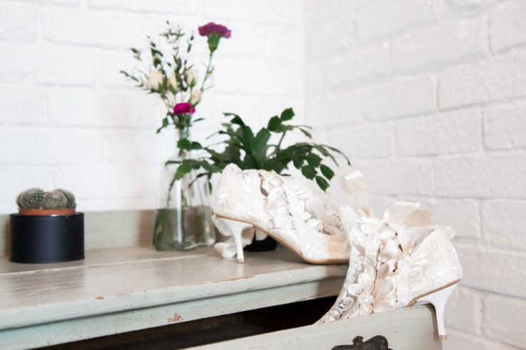 Lace bridal shoes in a vintage green dresser