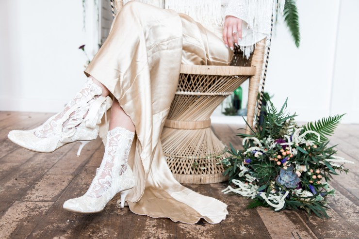 Bride in gold dress sat on bohemian peacock chair