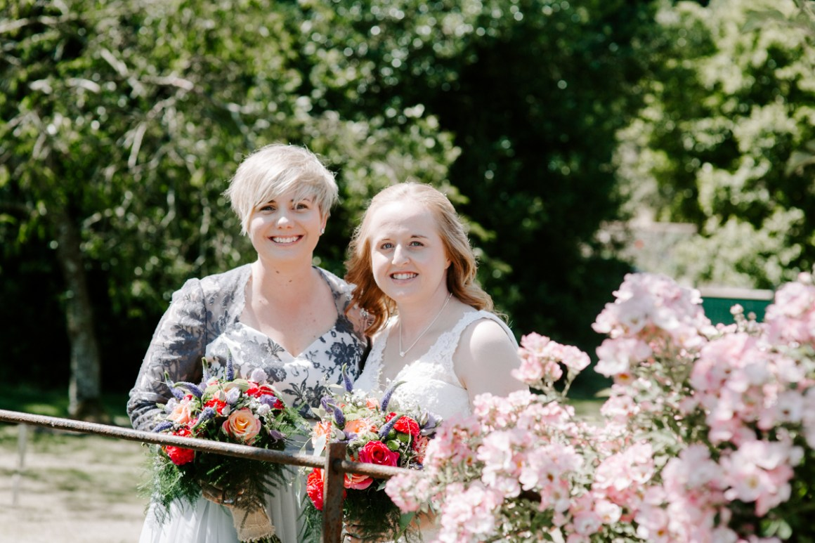 Two brides holding bright bouquets
