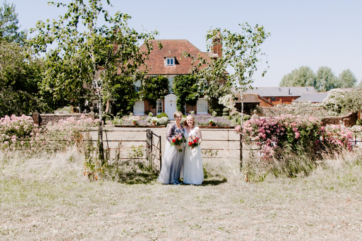 Brides standing in front of Dummer Down farm wedding venue