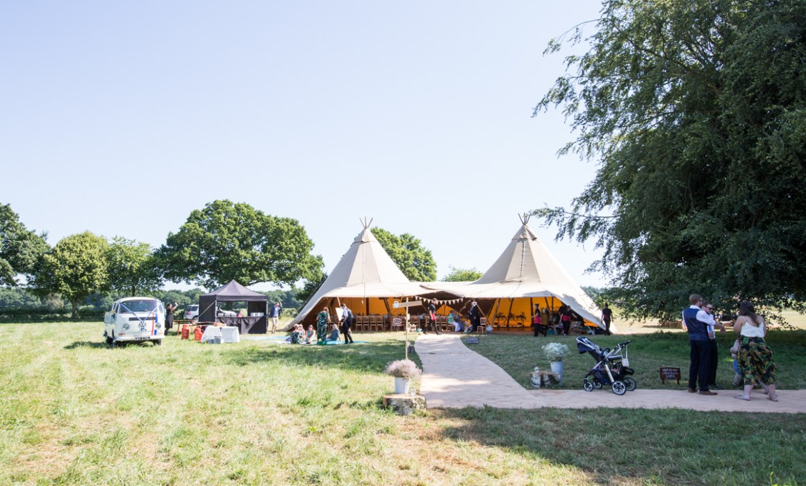 Tipi in a field for a sunny wedding day
