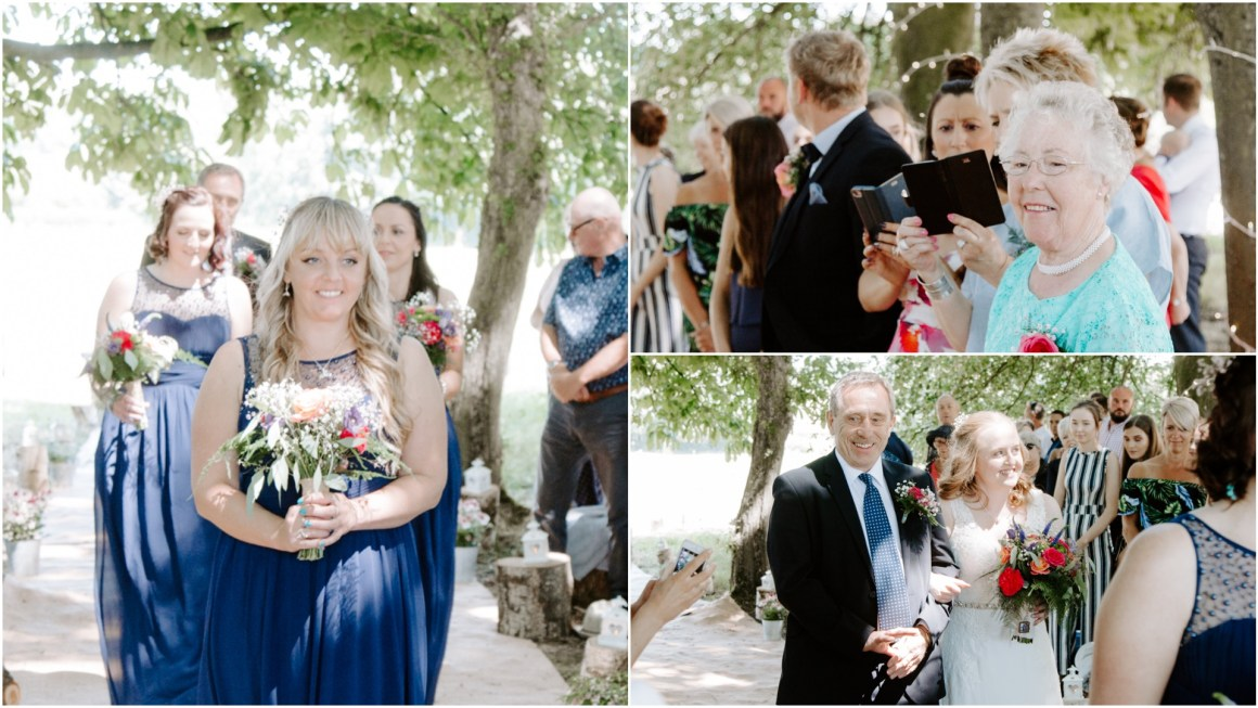 Bridesmaids in navy dresses walking down an outdoor aisle