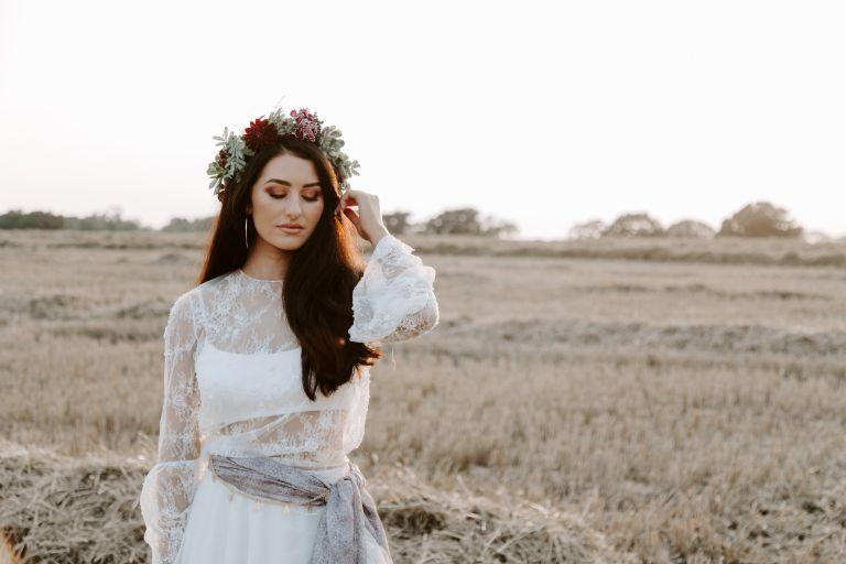 Bohemian bride with a floral crown at sunset