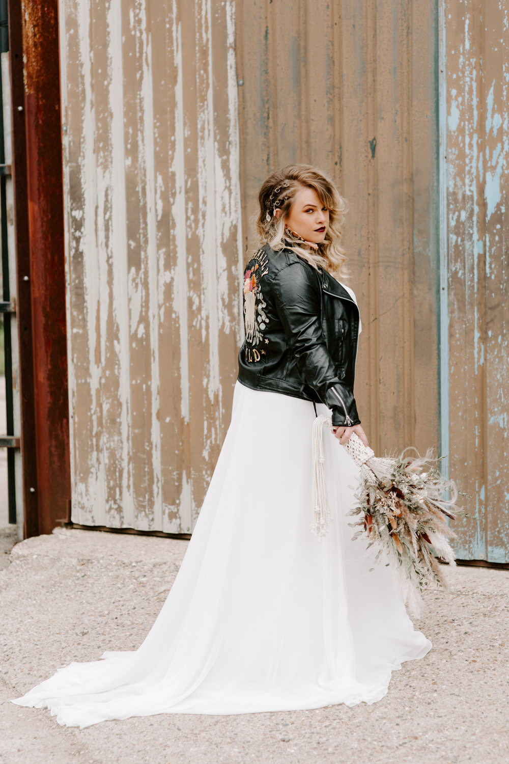 Bride wearing leather jacket at Barns at Lodge Farm