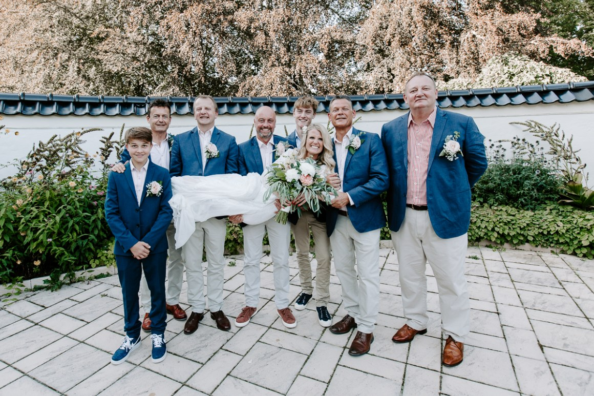 Groomsmen holding the bride in the air