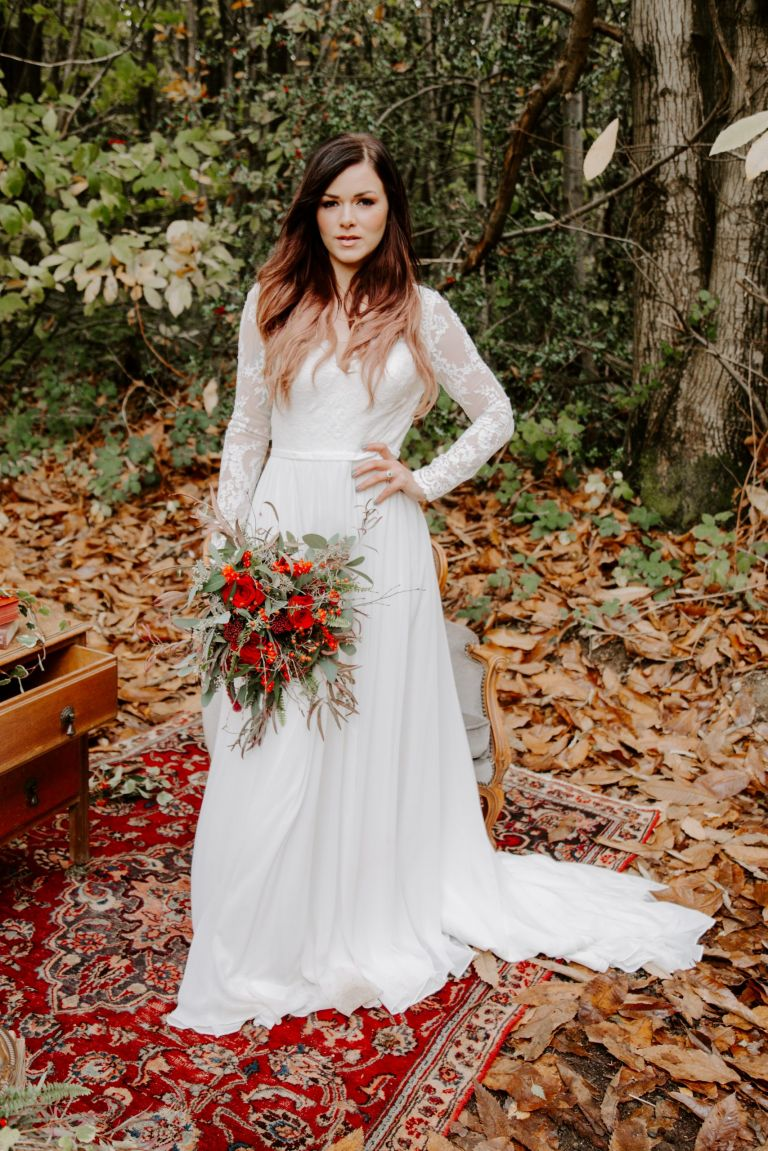 A bride stood in the leaves at Longton Wood