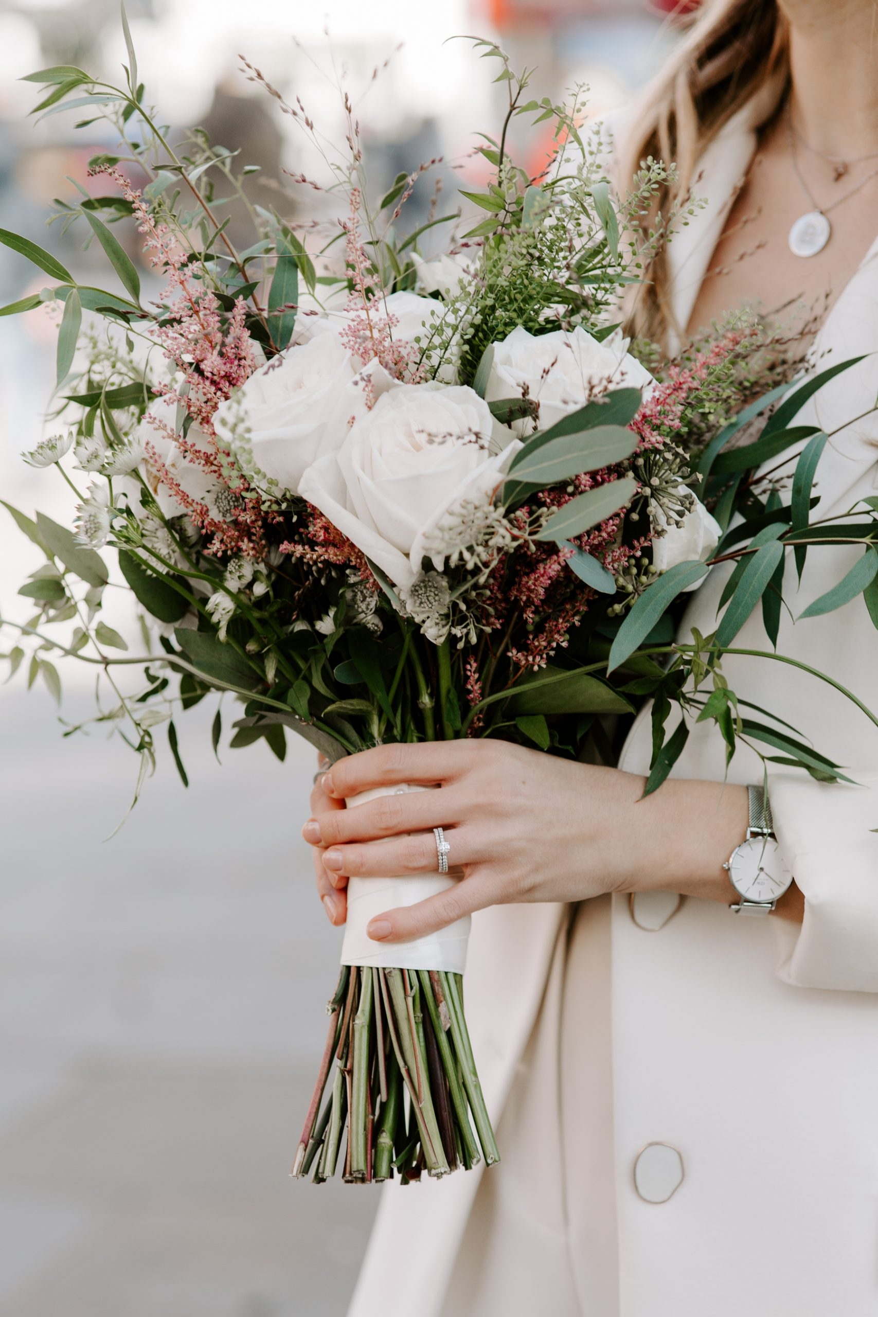 A bride holding a modern white and eucalyptus wedding bouquet