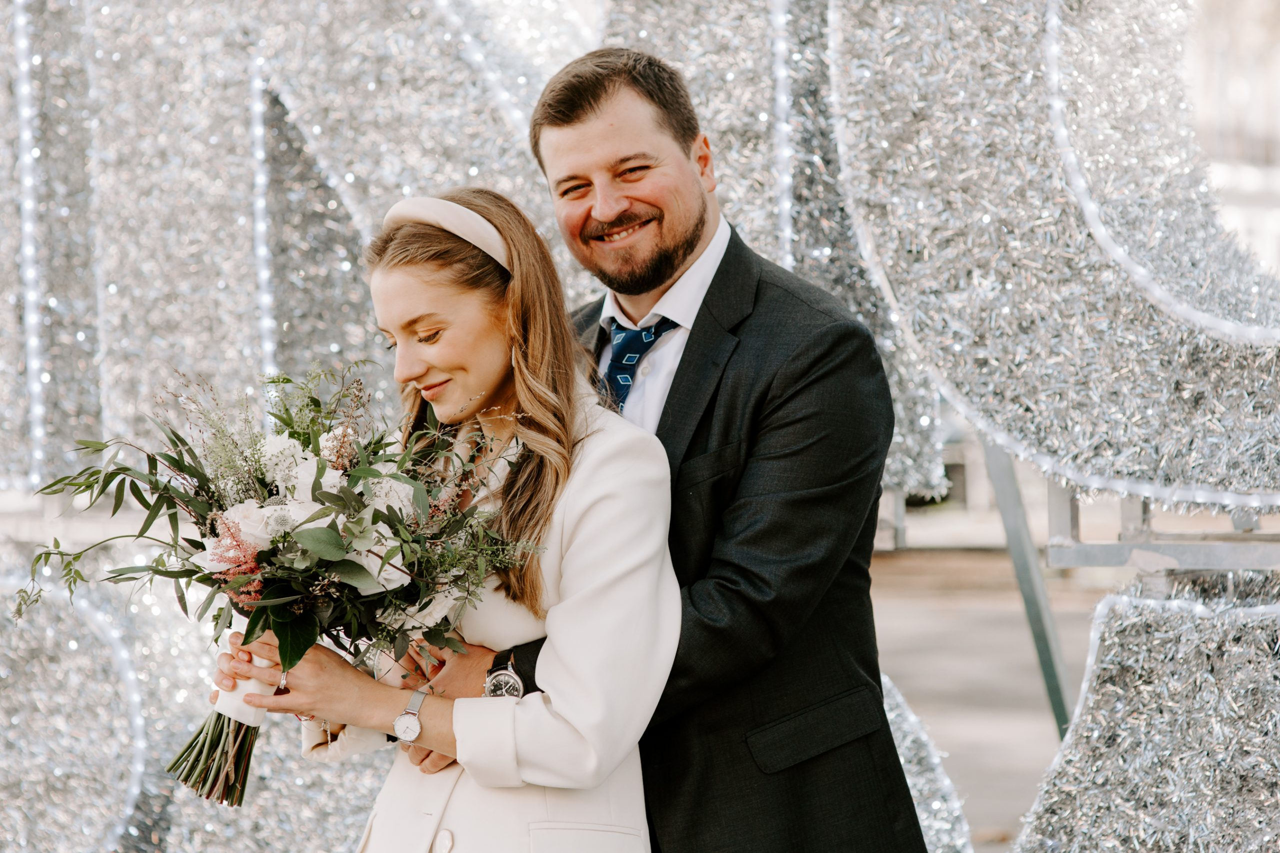 Bride and groom in front of sparkly Christmas backdrop