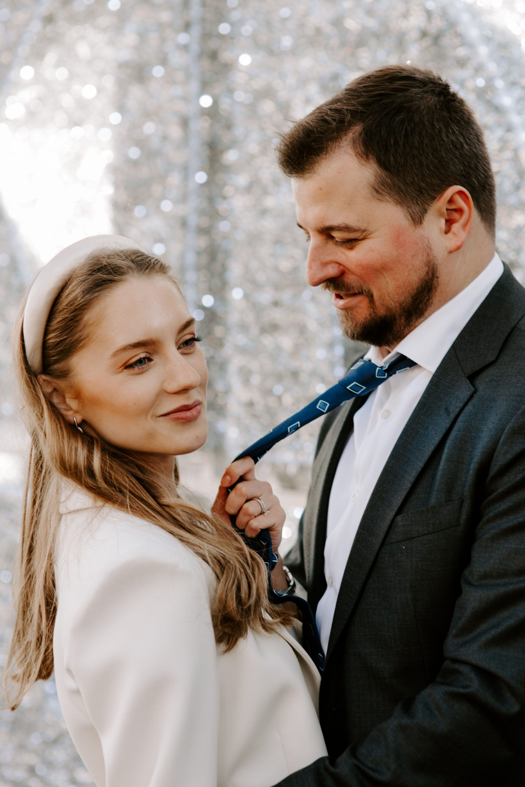 Bride pulling her groom to her with tie