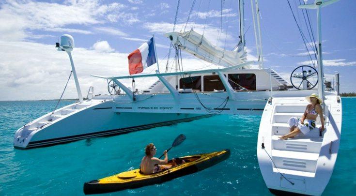 Kayaking up to woman lounging on steps of 82ft sailing yacht Catamaran Magic Cat