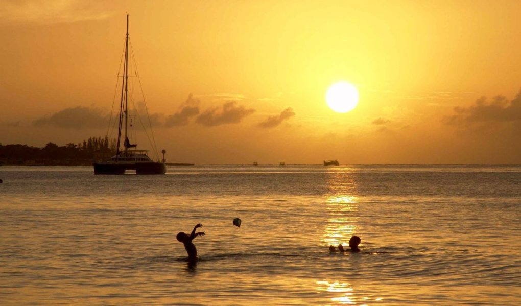Father and son playing ball in water near Catamaran at golden Caribbean sunset