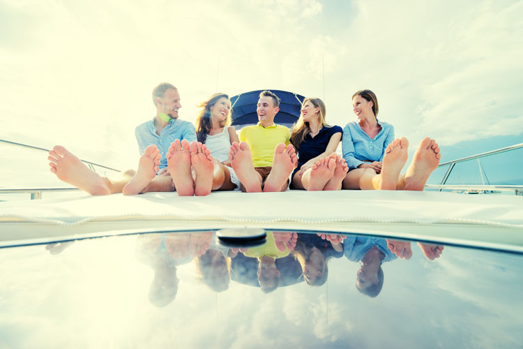 Millennial friendship and vacation. Group of laughing young people sitting on the yacht deck sailing the sea.
