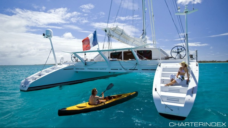 Kayaking up to woman lounging on steps of 82ft sailing yacht Catamaran Magic Cat