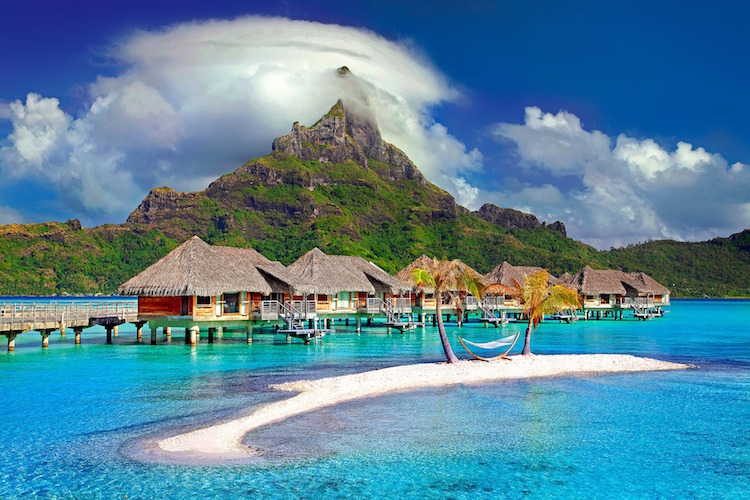 Hammock between two palm trees near cottages on stilts in Bora Bora, French Polynesia blue water mountain peak with clouds