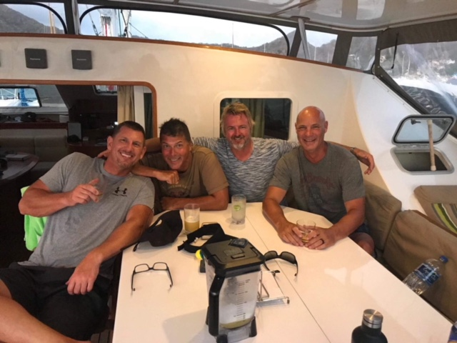 Four men at table inside sailing catamaran Adastra