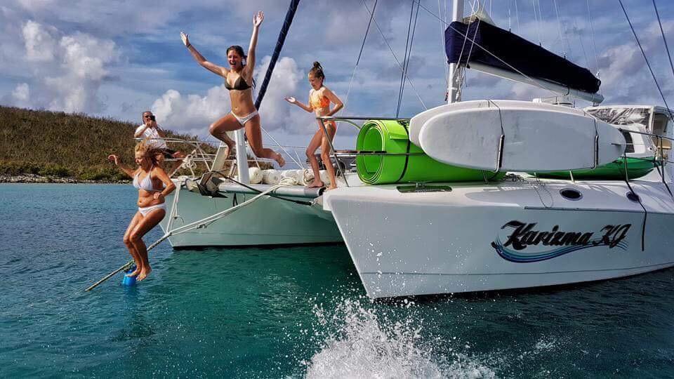 Happy family jumping off the 53ft Royal Cape catamaran KARIZMA