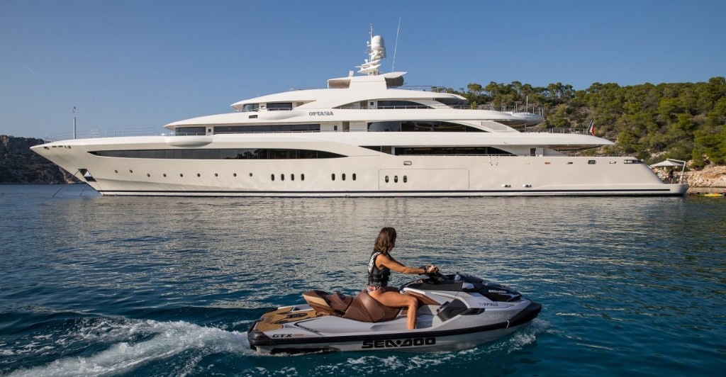 MainShot 279ft Golden Yacht motor yacht O'ptasia with women on jet ski. Operating in the East Mediterranean, West Mediterranean, Arabian Gulf, Caribbean and the Indian Ocean