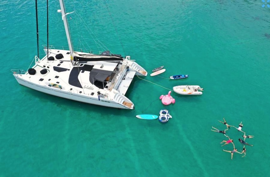 65ft Sailing catamaran Lolalita in blue-green water with toys and circle of floating friends and family