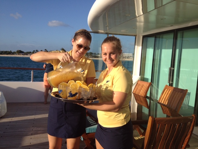 Charter yacht crew pouring iced orange drinks for passengers in St. Barths in the Caribbean