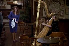 Photo of Kirstie Alley standing near Carol Robbins playing her harp in TV show Cheers Season 8, Episode 16, Finally