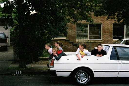 Local children find a good vantage spot in the back of a ute along The Kingsway © Carolyn M Cash