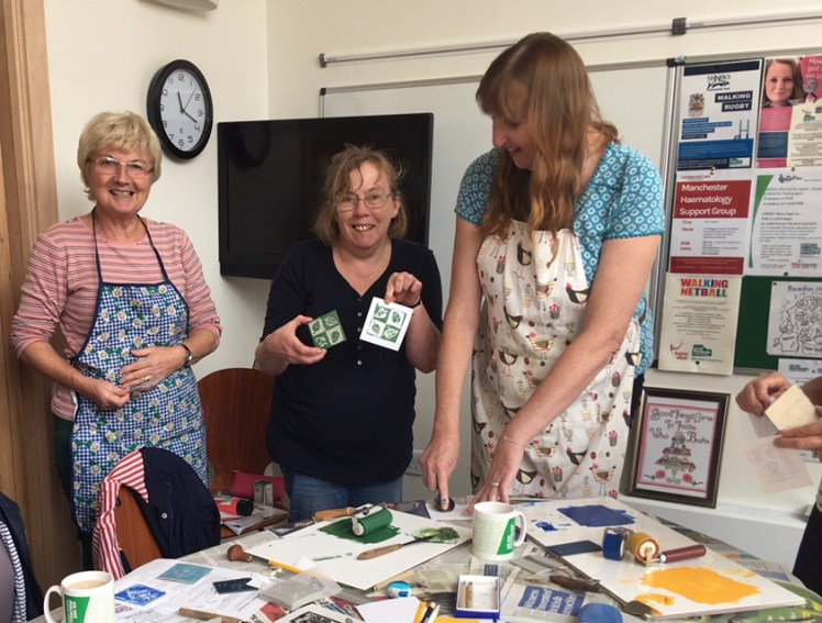 Image of members of Macmillan Craft & Chat group and their linocut work