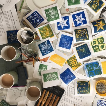 Image of a lots of linocut works on the table amongst cups of tea and linocutting tools