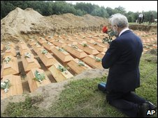 A man prays in front of coffins during the reburial ceremony in the village of Stare Czarnowo, Poland, 14 August 2009