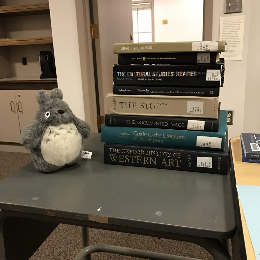This is a stack of books I read to learn about being an art librarian next to my stuffed Totoro