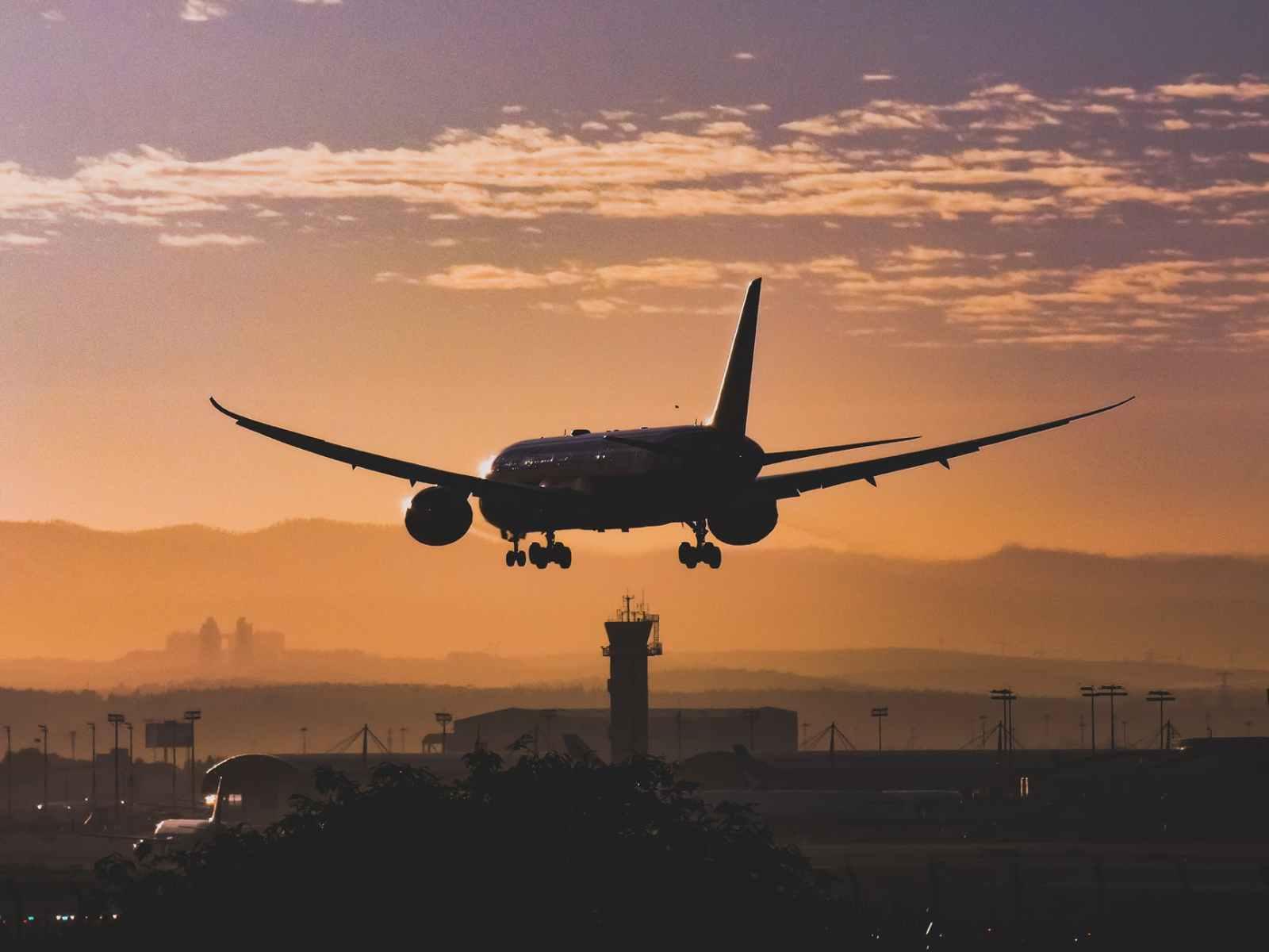 white passenger plane flying over the city during sunset