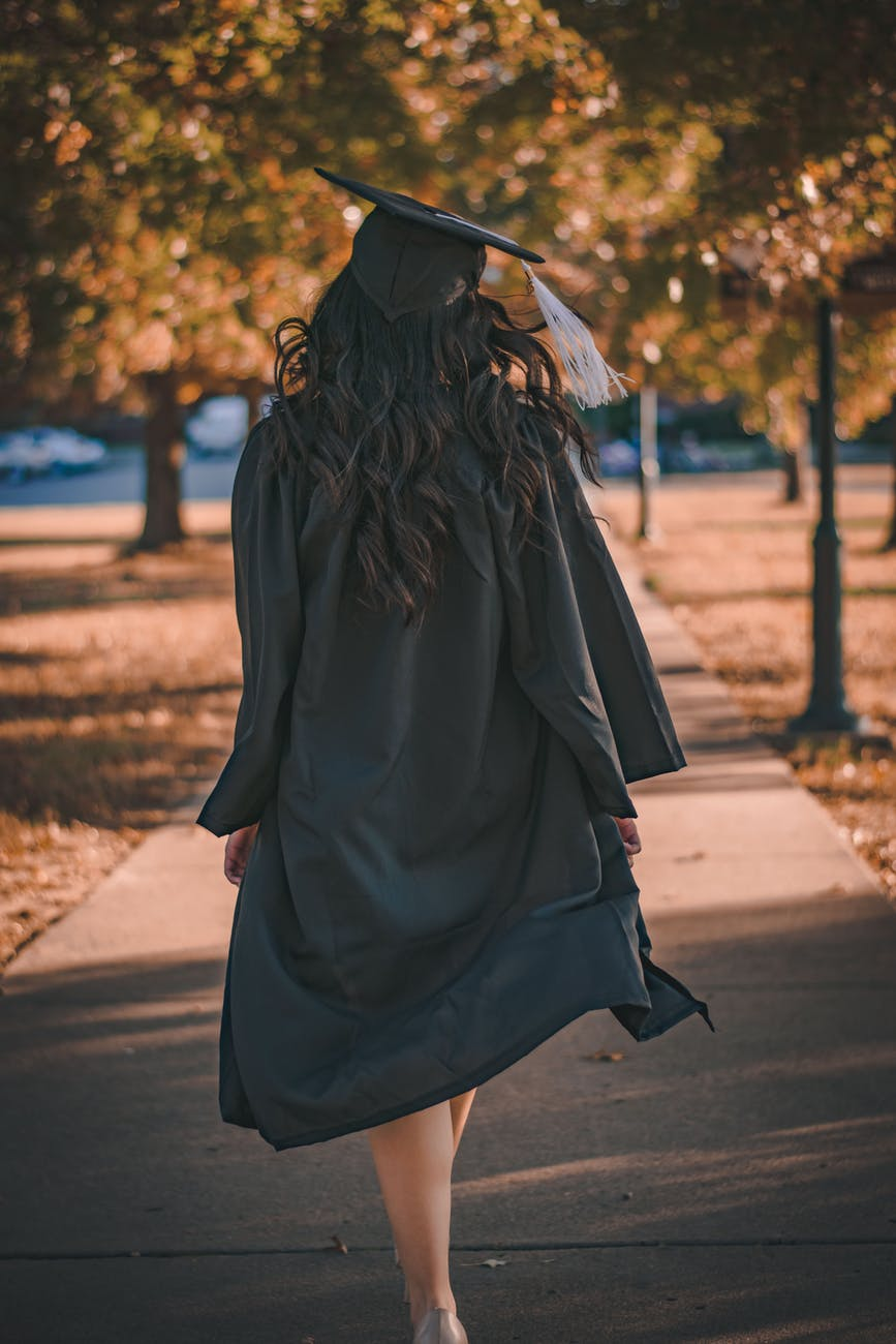 woman in black long sleeve dress standing on brown concrete pathway