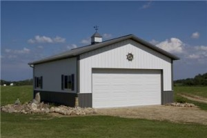 steel buildings garage type two tone white on green with roll up door and windows.