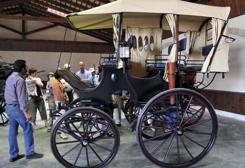 Miguel and several members of the group look at an unusual, recently restored American carriage