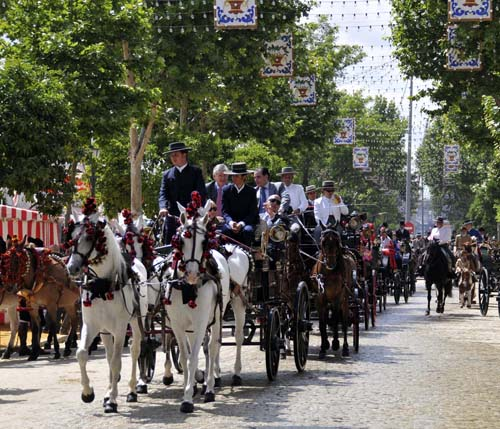 a long line of horse-drawn carriages parading down the streets of the feria