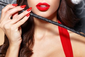 Sexy brunette santa woman with whip closeup