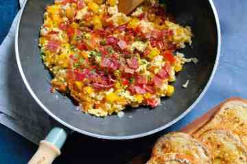An easy and healthy way to upgrade your scrambled eggs - peppers, tomatoes, cheese, bacon and a sprinkle of chilli make these Fiesta Scrambled Eggs a party on your plate.